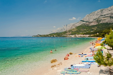 Amazing beach with people in Tucepi Croatia. Tucepi is a popular holiday resort in Croatia Stock Photo