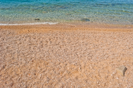 Waves on beautiful beach with pebbles in Makarska Riviera in Podgora Croatia