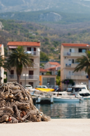 Pile of fishing nets with floats on a quay with blurred boats on background. Podgora Croatia. Vertical photo Stock Photo