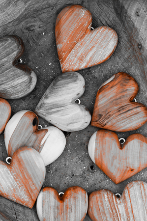 Some wooden heart shapes on brown background. Black and white photo