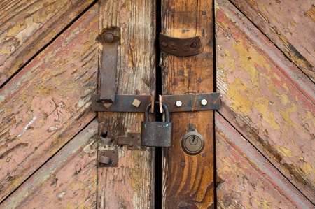 secure growth: Rusty old padlock locking a wooden door Stock Photo