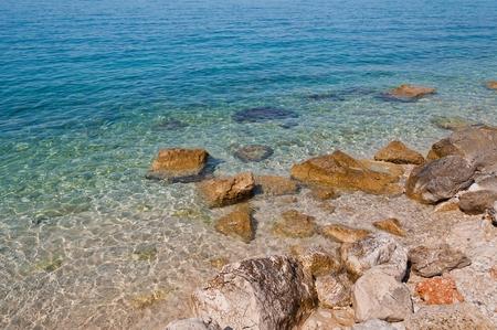 Beautiful beach with big stones and crystal clear adriatic sea. Podgora, Croatia