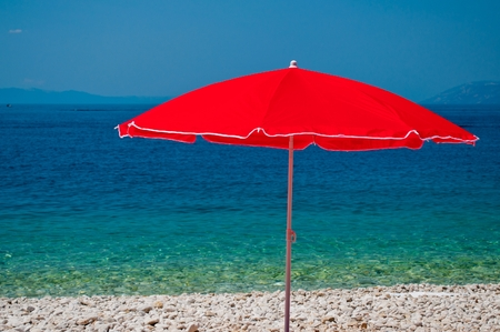 Beach with pebbles and red sunshade with sea in background on a summer day