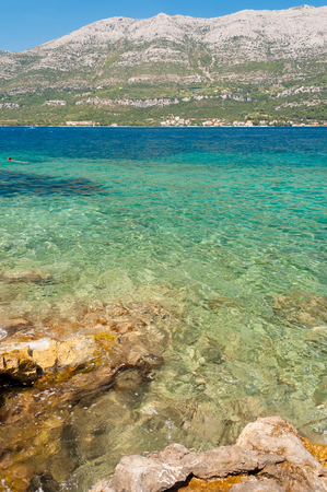 Amazing beach with stones in Kocula, Croatia. Adriatic sea with turquoise color. Vertical photo Stock Photo