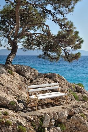 White bench on stones under the tree, with sea in background. Podgora, Croatia Stock Photo