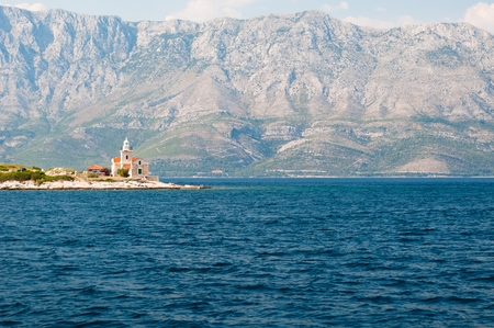Lighthouse on the south end of island Hvar in the Adriatic sea with mountain Biokovo in background. Sucuraj, Croatia