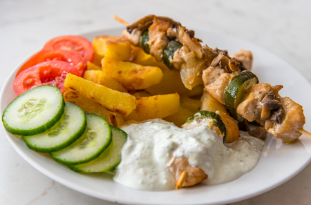 the shish kebab: Traditional delicious chicken shish kebab with mushrooms. Served with American potatos, cucumber, tomatoes and tzatziki dressing