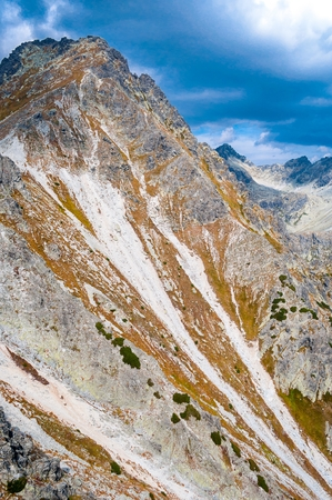 View of mountains from Solisko in High Tatras in Slovakia with cloudy blue sky. Vertical photo