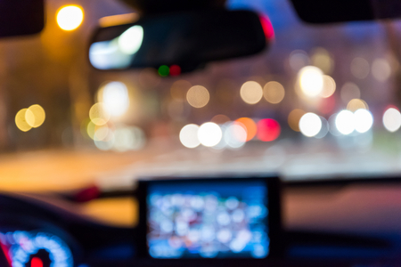 Inside car with bokeh lights from traffic jam on night time for background. Blur image