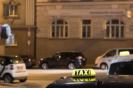Taxi cab sign on top of the vehicle at nighttime. Vienna, Austria Stock Photo