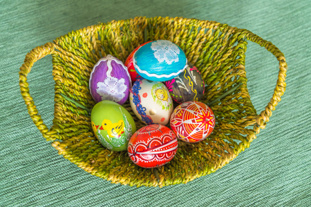 Beautiful colorful hand painted easter eggs in basket. Top view Stock Photo
