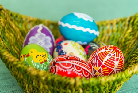 Closeup of beautiful colorful hand painted easter eggs in basket. Selective focus Stock Photo