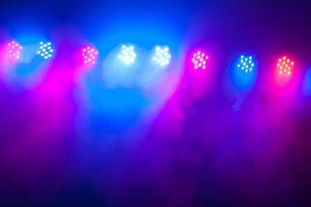 Spotlights and illumination equipment with fog on stage. Concert lighting as background