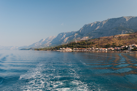 Adriatic sea at Podgora in Croatia with high mountain Biokovo and monument Seagull's wings in background Stock Photo