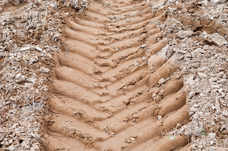 dirtroad: Tractor wheel tracks on the ground as background