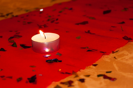 One burning candle (tea light) on a red tablecloth. Space on right side