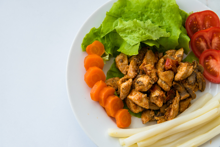 Fried chicken meat served on plate with white asparagus, carrot, tomato and lettuce. Top view. Space on left side. Stock Photo