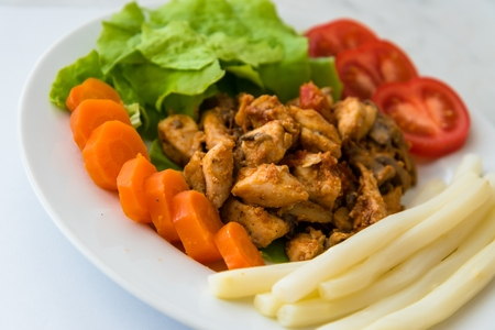 Fried chicken meat served on plate with white asparagus, carrot, tomato and lettuce. Selective focus.