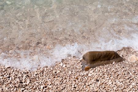 Stones on the beach with wave. Podgora, Croatia
