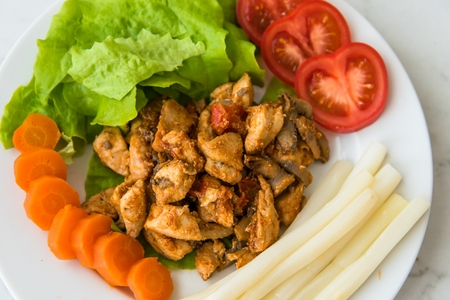 Fried chicken meat served on plate with white asparagus, carrot, tomato and lettuce. Top view Stock Photo