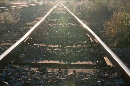 Detail of railway tracks with girder and gravel against sunshine Stock Photo