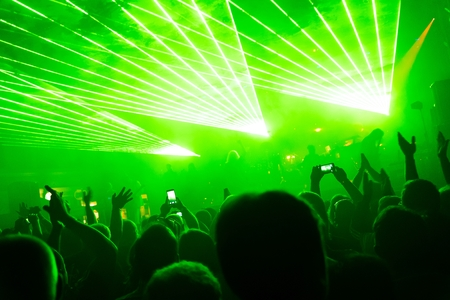 Rock concert, silhouettes of happy people raising up hands in front of bright, green stage laser lights. Space in top side.
