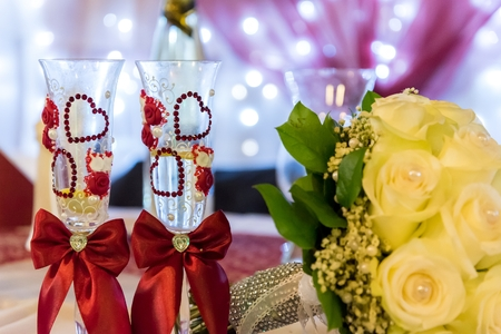 Yellow bride's bouquet with two wedding wine glasses decorated with hearts. Wedding decoration