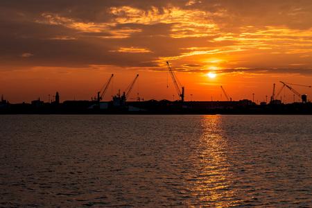 Silhouette of sea port cranes in the morning at sunrise. Chioggia, Italy