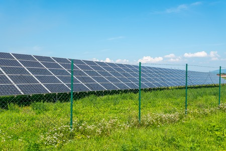 Solar panels in the field with blue sky. Photovoltaic modules produces green, environmentally friendly, renewable energy from the sun.