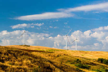 Wind turbines generating electricity on the field under the blue clouded sky. Renewable electric energy production.