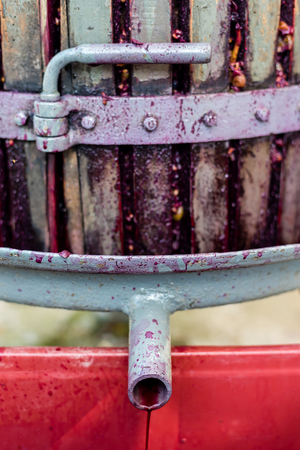 Wooden wine press with red must for pressing grapes to produce wine. Traditional old technique of wine-making. Vertical photo