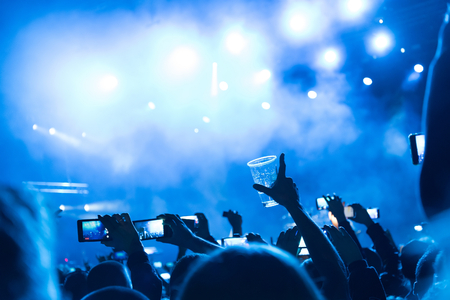 Rock concert, silhouettes of happy people raising up hands in front of bright stage lights. Space in top side.