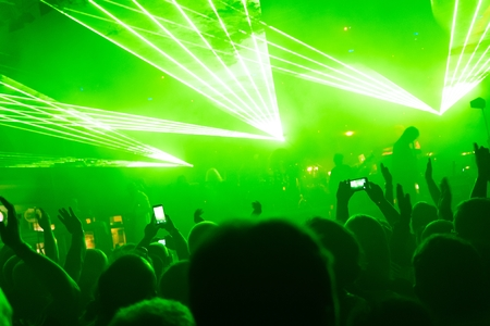 laser lights: Rock concert, silhouettes of happy people raising up hands in front of bright, green stage laser lights. Space in top side.