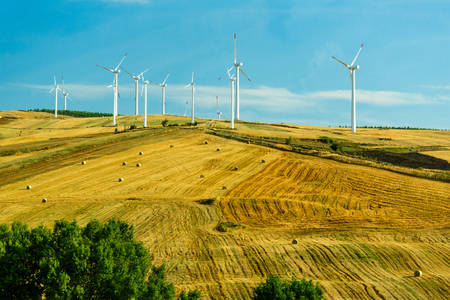 Wind turbines generating electricity on the field under the blue clouded sky. Renewable electric energy production. Italy Stock Photo