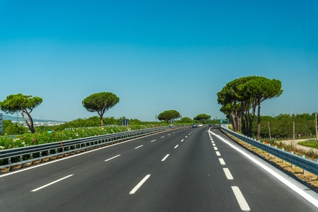 View of the highway with trees and blue sky in Italy