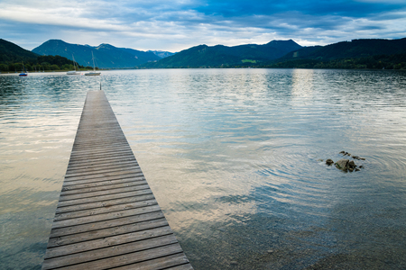 Picturesque view of wooden pier in the beach of Tegernsee lake near Gmund am Tegernsee in Germany. Space in right side