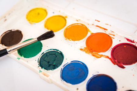 The palette of watercolor paint and one brush on white sheets of paper