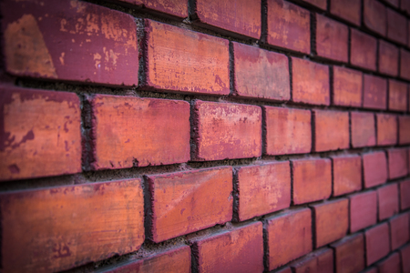Detail of red brick wall background in perspective view. Selective focus