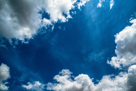 Blue sky background with white clouds. Space in center