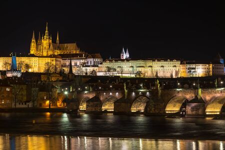 The Prague castle with historic Charles Bridge and Vltava river in the night scene with water reflection. Prague is a popular travel destination. Prague, Czech Republic