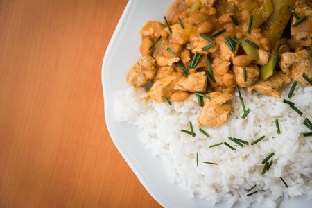 Chicken curry nuggets with rice and bean on a white plate. Space on left side