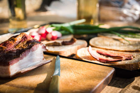 Bacon and knife on a wooden desk. Grilled bacon slice on fatty bread, green onion and fresh radish in the background on a hungarian summer grill party. Barbecue background