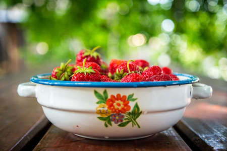 Plate with group of ripe, delicious strawberry on a brown wooden table. Selective focus. Shallow DOF. Blurred natural background