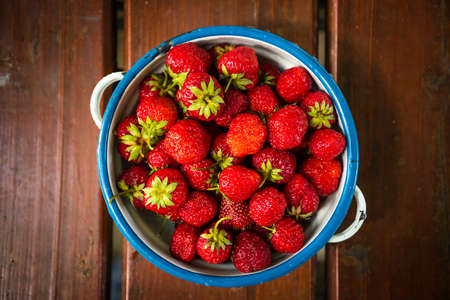 Plate with group of ripe, delicious strawberry on a brown wooden table. Top view. Stock Photo - 151372463