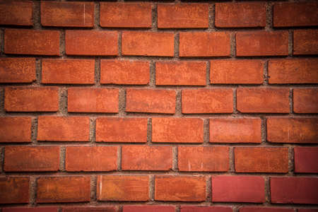 Detail of red brick wall background with dark vignette in corners