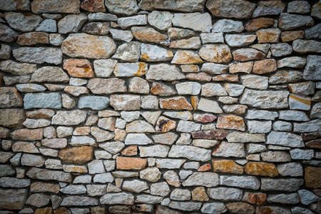 Stone wall background of colorful stones with vignetted borders