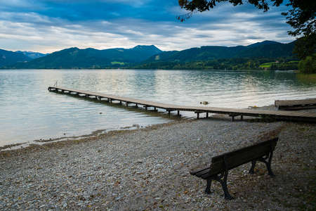 Wooden pier and bench in the beach of Tegernsee lake near Gmund am Tegernsee in Germany Stock Photo