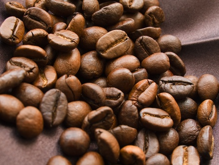 Roasted coffee beans on brown textile