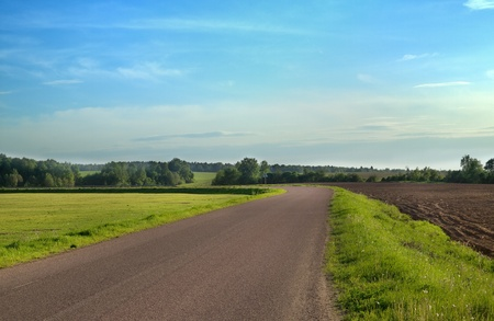Countryside view with road and field under blue sky