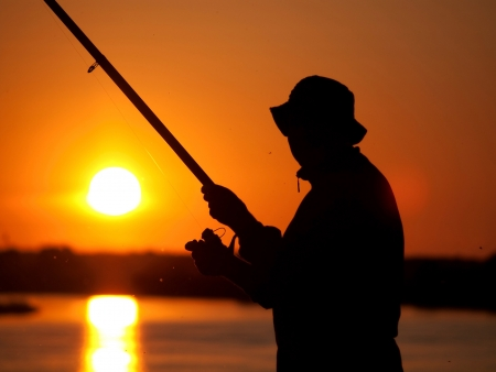 Silhouette of a fisherman on sunset